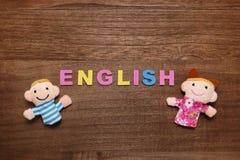 El alfabeto pone letras a INGLÉS y a las muñecas de los niños en la madera Fotografía de archivo libre de regalías