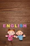 El alfabeto pone letras a INGLÉS y a las muñecas de los niños en la madera Foto de archivo