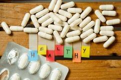 El alfabeto sano y la cápsula drogan con la dosis de la medicina en el fondo de madera Fotos de archivo