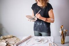 El alfarero de la mujer bastante joven pinta una taza de la arcilla Mujer que trabaja en su estudio de la cerámica Imagen de archivo libre de regalías