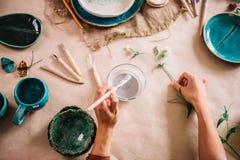 El alfarero de la mujer bastante joven pinta una taza de la arcilla Mujer que trabaja en su estudio de la cerámica Imágenes de archivo libres de regalías