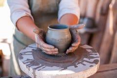 El alfarero está creando la loza de barro en la rueda del ` s del alfarero foto de archivo libre de regalías