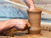 El alfarero hace un florero de la arcilla en una rueda de la cerámica foto de archivo