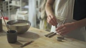 El alfarero joven está haciendo el detalle de la arcilla en la tabla en taller de la cerámica metrajes
