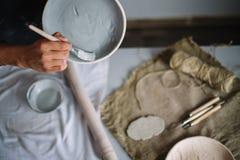 El alfarero moldea una taza de arcilla El alfarero joven adorna una taza de arcilla Imagenes de archivo