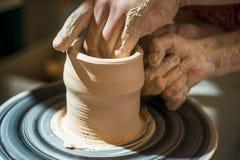 El alfarero principal enseña el niño a cómo hacer un jarro fuera de la arcilla Imagen de archivo