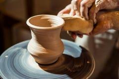 El alfarero principal enseña el niño a cómo hacer un jarro fuera de la arcilla Fotografía de archivo libre de regalías