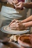 El alfarero principal enseña el niño a cómo hacer un jarro fuera de la arcilla Fotos de archivo libres de regalías