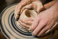 El alfarero principal enseña el niño a cómo hacer un jarro fuera de la arcilla Foto de archivo