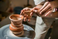 El alfarero principal enseña el niño a cómo hacer un jarro fuera de la arcilla Imagen de archivo libre de regalías
