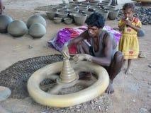 El alfarero trabaja la arcilla en una rueda Imagen de archivo libre de regalías