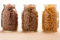El alforfón del trigo y las pastas deletreadas se separaron en tres tarros de cristal Fotos de archivo libres de regalías