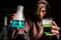 El alquimista en laboratorio químico prepara líquidos mágicos Imagen de archivo