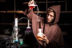 El alquimista en laboratorio químico prepara líquidos mágicos Imagen de archivo libre de regalías