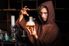 El alquimista en laboratorio químico prepara líquidos mágicos Fotos de archivo