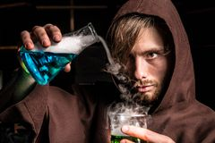 El alquimista en laboratorio químico prepara líquidos mágicos Foto de archivo libre de regalías