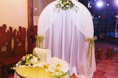 El altar blanco de la boda adornado con las cintas verdes se coloca en el r Imagenes de archivo