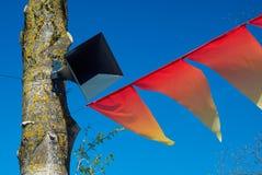 El altavoz en árbol en fondo del cielo azul y de las banderas rojas del día de fiesta Imagenes de archivo