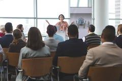 El altavoz femenino con el ordenador portátil habla en un seminario del negocio imagen de archivo libre de regalías