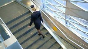 El alto asistente de vuelo, calzado en tacones altos, sube para arriba la escalera almacen de metraje de vídeo