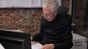 El alto directivo trabaja en el ordenador que se sienta en el lugar de trabajo en compañía grande almacen de video