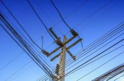 El alto voltaje y el cable de los posts de la electricidad alinean en el cielo azul Fotos de archivo libres de regalías
