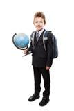 El alumno en el traje de negocios que sostiene el globo de la tierra y la escuela hacen excursionismo Foto de archivo