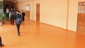 El alumno en la escuela va a lo largo del pasillo almacen de metraje de vídeo
