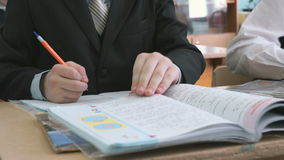 El alumno escribe el texto en el cuaderno almacen de video