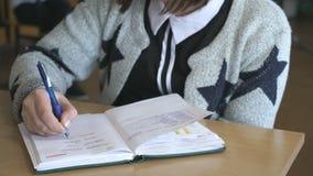 El alumno escribe el texto en el cuaderno dentro almacen de metraje de vídeo