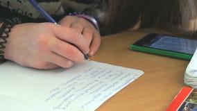 El alumno escribe el texto en la hoja de papel blanca almacen de video