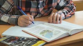 El alumno escribe el texto en libro de ejercicio en la lección almacen de metraje de vídeo