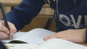 El alumno escribe el texto en un cuaderno dentro almacen de metraje de vídeo
