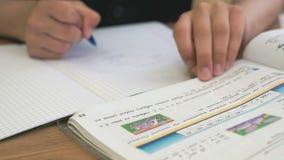 El alumno escribe el texto en un cuaderno en la lección almacen de video