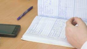 El alumno escribe el texto en un diario de la escuela dentro almacen de metraje de vídeo