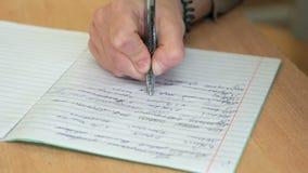 El alumno escribe en un cuaderno en la sala de clase almacen de metraje de vídeo