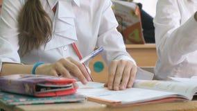 El alumno escribe la extensión en un cuaderno usando pluma de bola almacen de metraje de vídeo