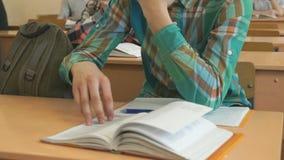 El alumno lee el libro de texto de la escuela en la lección metrajes