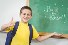 El alumno sonriente que muestra de nuevo a escuela firma en la pizarra Imagenes de archivo