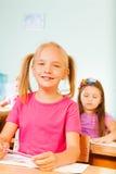 El alumno sonriente sostiene el lápiz y se sienta en el escritorio Fotografía de archivo libre de regalías
