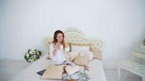 El ama de casa bebe el té, sentándose en cama grande en casa Imagenes de archivo