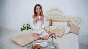 El ama de casa bebe el té, sentándose en cama grande en casa Fotografía de archivo libre de regalías
