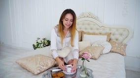 El ama de casa bebe el té, sentándose en cama grande en casa Fotografía de archivo