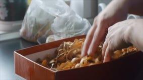 El ama de casa clasifica cebollas en el primer de las manos de la cocina metrajes