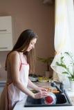 El ama de casa de la muchacha lava platos sucios en la cocina foto de archivo libre de regalías