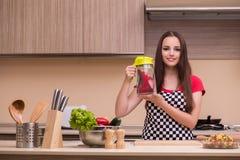 El ama de casa de la mujer joven que trabaja en la cocina Imagen de archivo libre de regalías