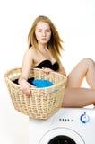 El ama de casa desnuda lava la ropa en un lavado Imagen de archivo