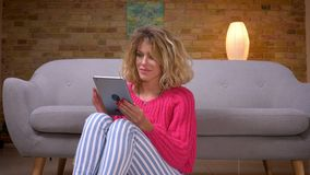 El ama de casa en suéter rosado se sienta en piso y muestra la pantalla verde de la croma de la tableta con la muestra del finger almacen de metraje de vídeo