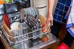 El ama de casa está haciendo los platos con el lavaplatos Imagen de archivo