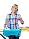 El ama de casa hermosa de la mujer planchó la ropa y el mostrar los pulgares para arriba Fotos de archivo